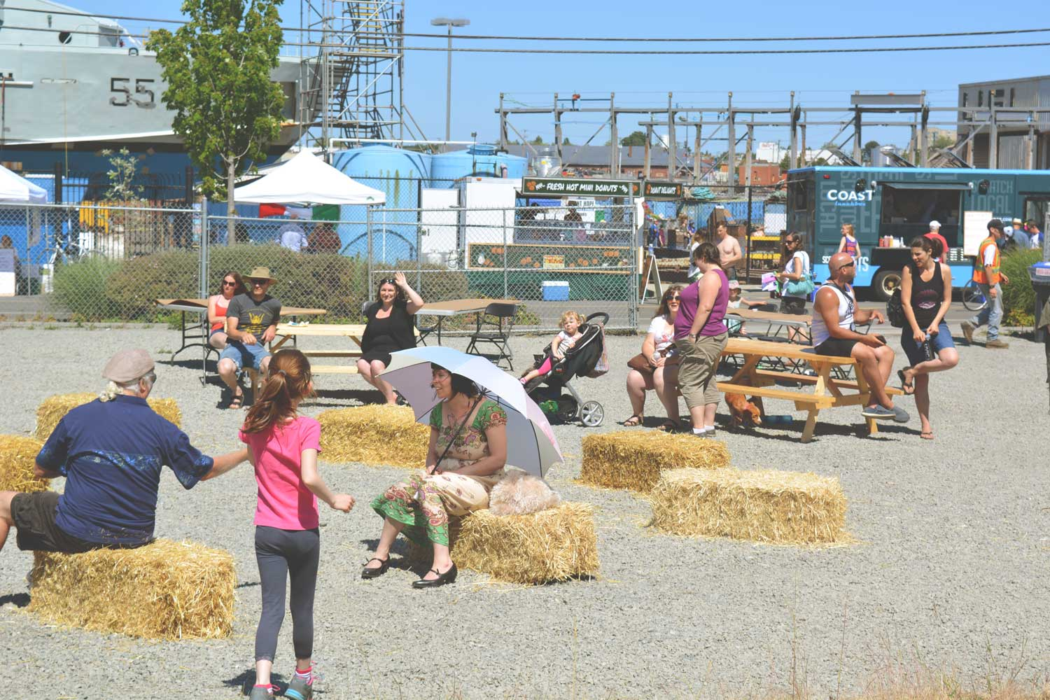 victoria west neighbourhood party with people sitting and talking on hay bales
